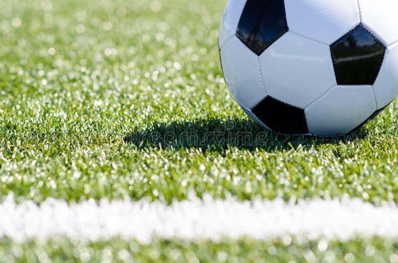 Balón de fútbol que se sienta en hierba cerca de la línea fotografía de archivo