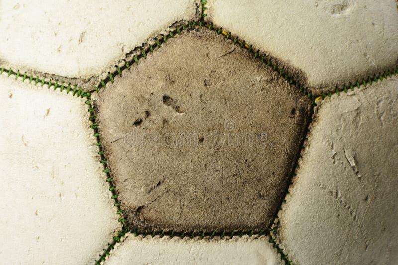 Balón de fútbol usado del vintage, fondo del primer con textura agrietada imagenes de archivo