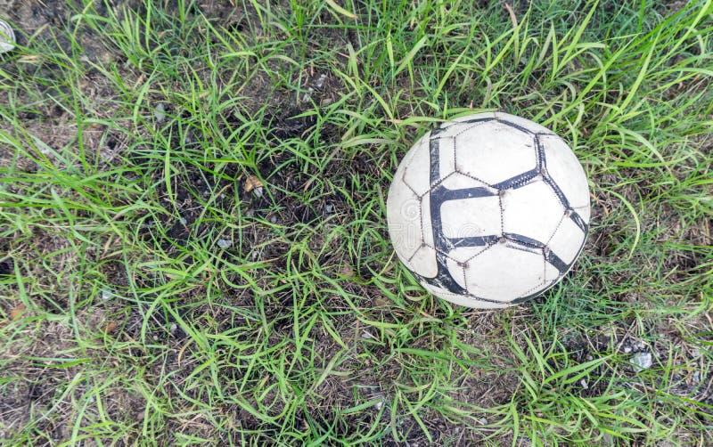 Balón de fútbol viejo en la hierba del campo de fútbol foto de archivo libre de regalías