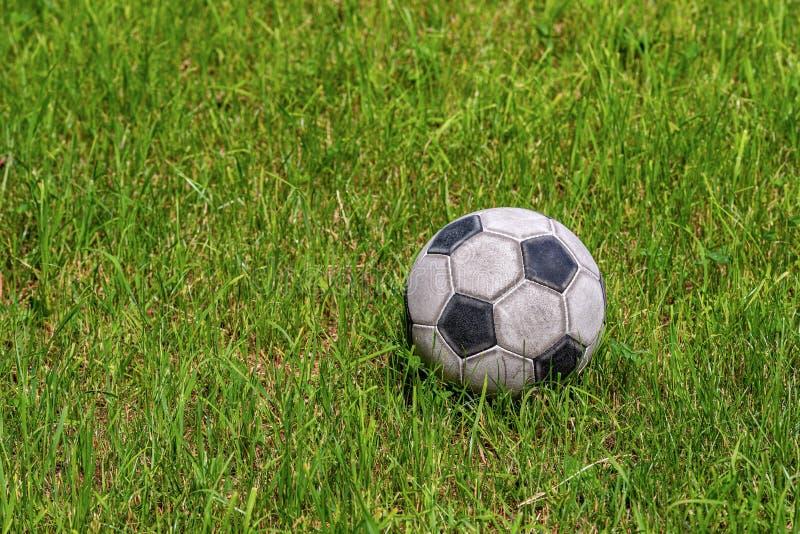 Balón de fútbol viejo en un prado verde - deporte del fútbol fotos de archivo libres de regalías