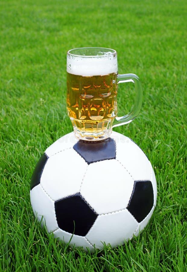 Balón de fútbol y taza de cerveza imagenes de archivo