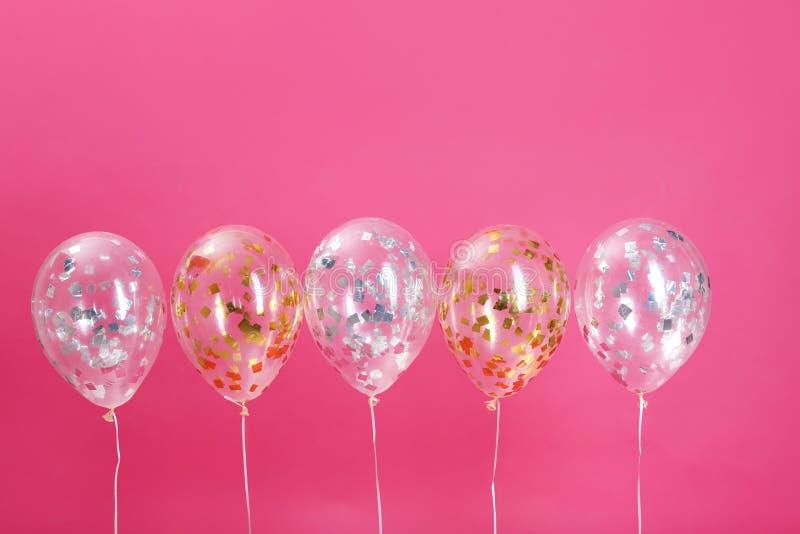 Balões brilhantes com sparkles no fundo da cor imagens de stock
