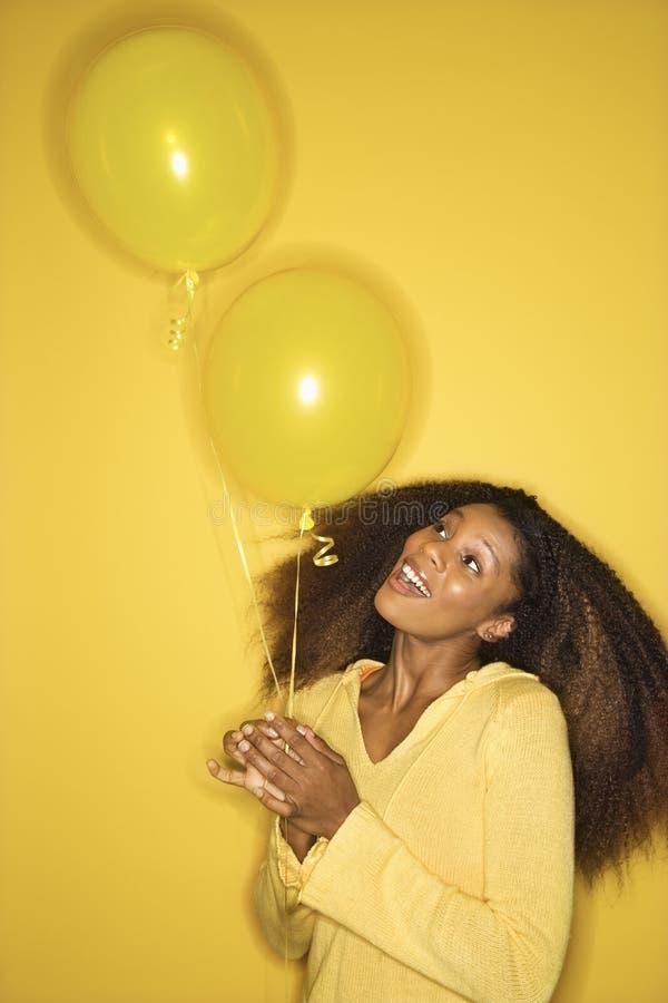 Balões da terra arrendada da mulher do African-American. imagem de stock royalty free