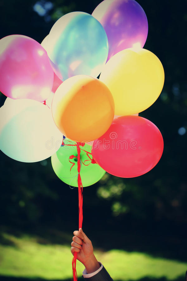 Balões de ar coloridos do feriado em uma mão foto de stock