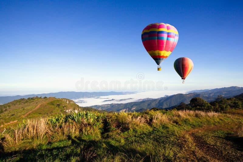 Balões de ar quente coloridos que voam sobre a montanha com nascer do sol e manhã Tailândia imagens de stock royalty free