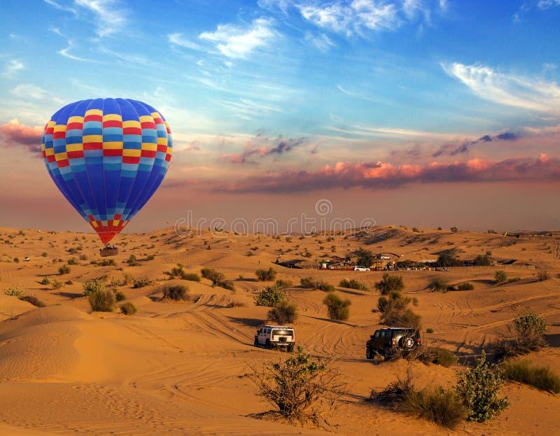 Balões de ar quente que aterram dunas de areia fora de estrada do carro da reunião no deserto foto de stock royalty free