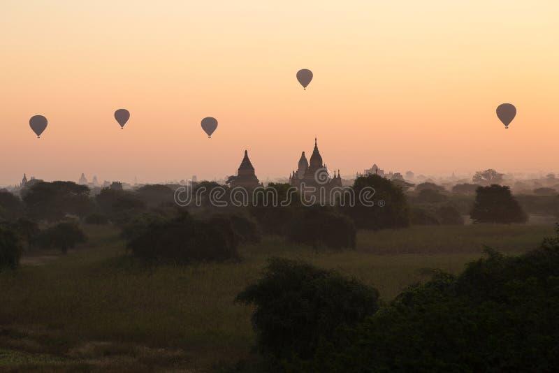 Balões de ar quente que flutuam sobre templos de Bagan contra o céu cor-de-rosa foto de stock royalty free