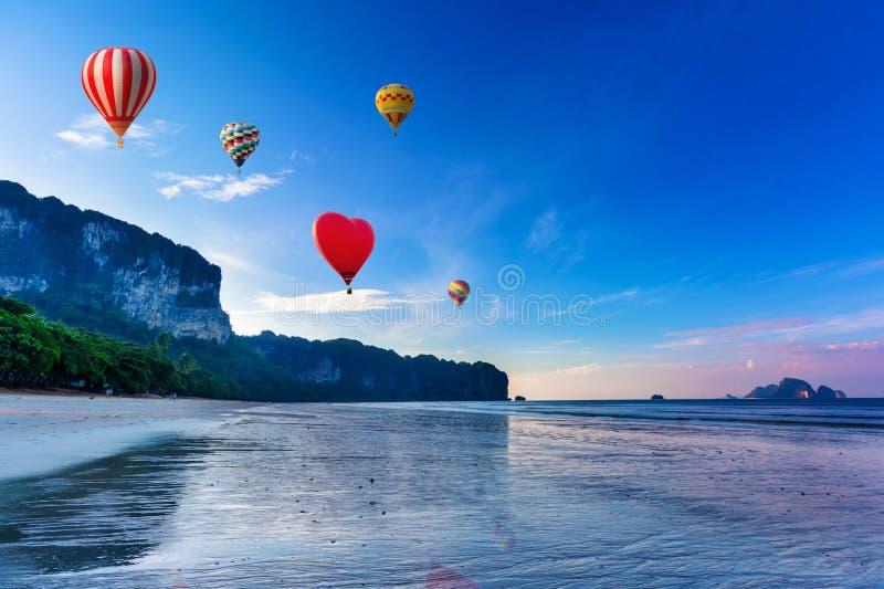 Balões de ar quente que voam sobre o por do sol na praia foto de stock royalty free