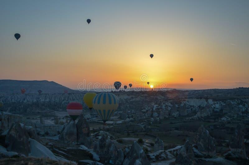 Balões de ar quente de Sunrice que aterram em uma montanha Cappadocia Goreme imagens de stock royalty free