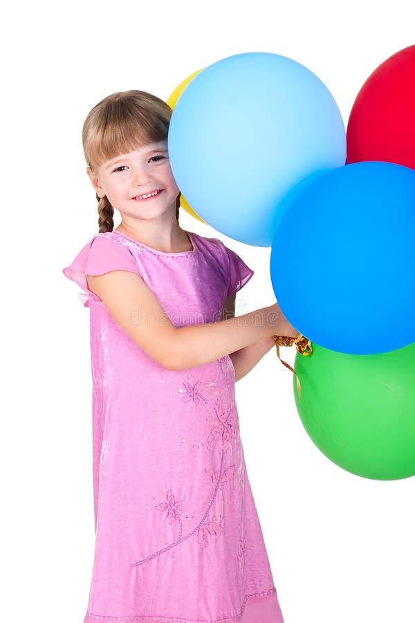 Balões de sorriso da terra arrendada da menina isolados no branco fotografia de stock