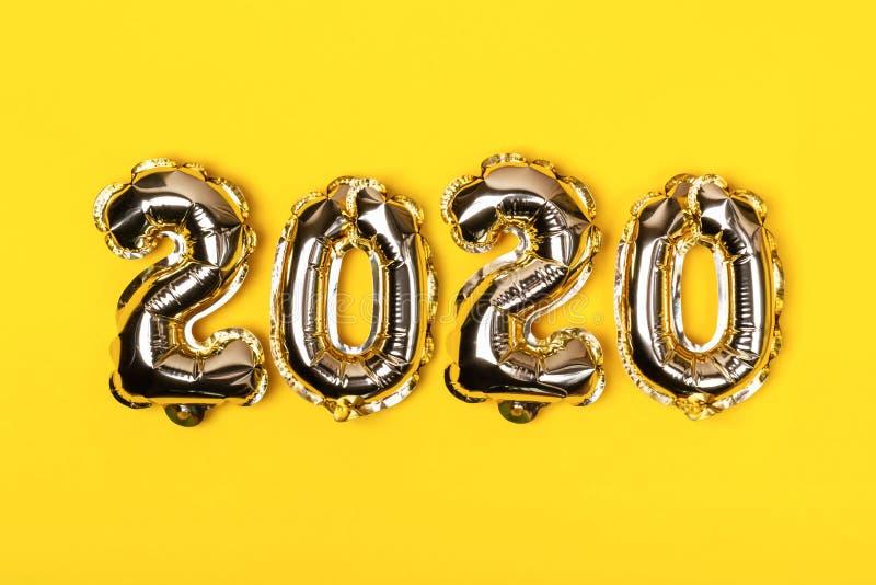 Balões dourados da folha no fundo amarelo Números infláveis 2020 Conceito do Natal foto de stock
