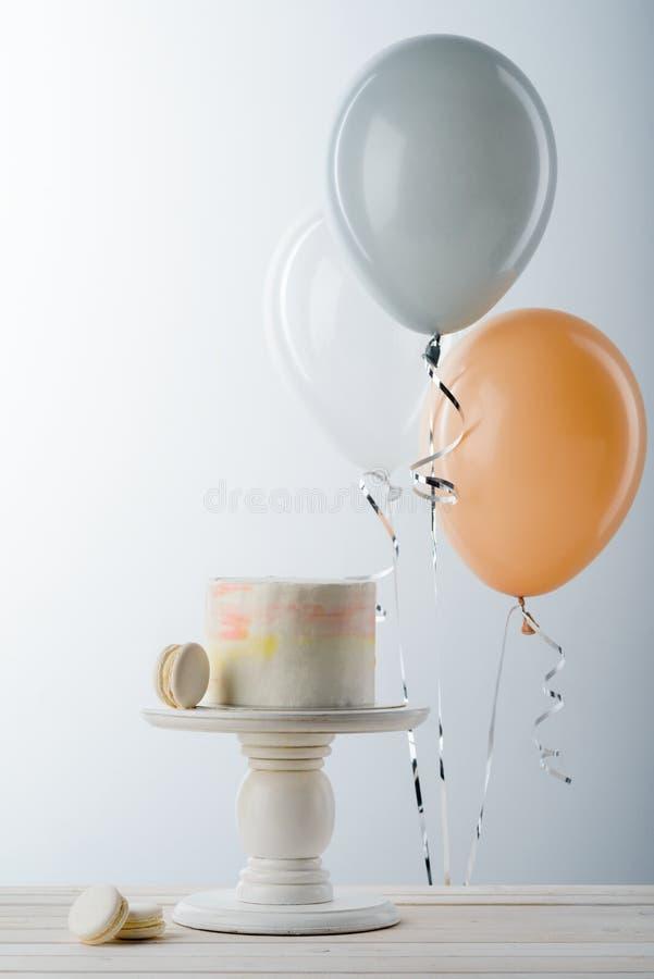 Balões e bolo no suporte fotografia de stock royalty free