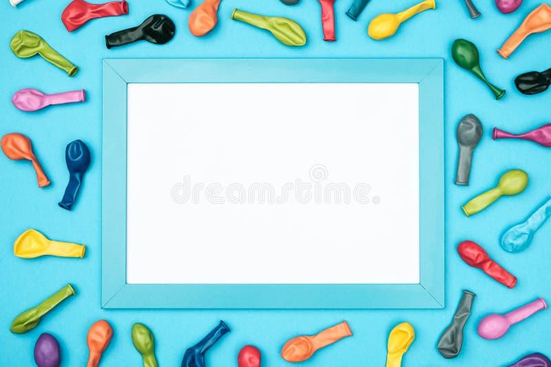 Balões e quadro coloridos na opinião superior do fundo colorido Modelo do aniversário ou do partido fotos de stock royalty free