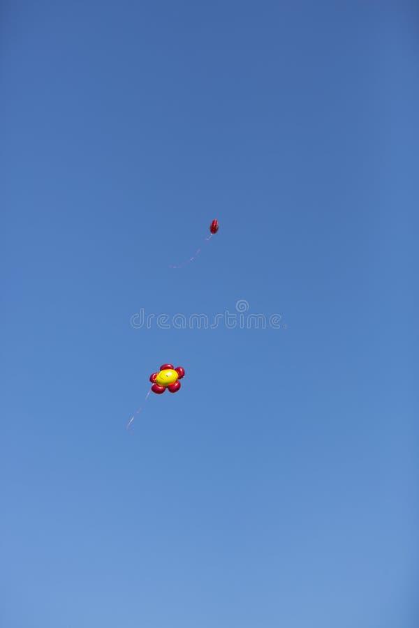 Balões vermelhos e amarelos que voam no céu azul fotos de stock