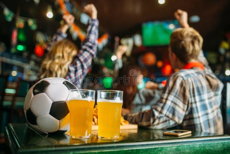 Bal en bier in sportenbar, spel het letten op concept stock foto