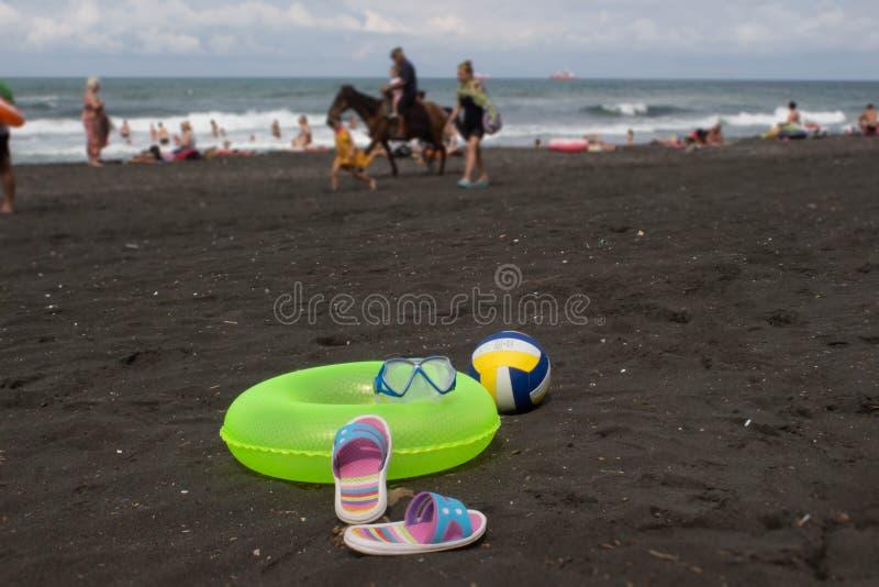 Bal, kleurrijk sandelhout en gele Drijvende Ring op strand Vage foto van mensen op zandstrand Concept van reis of het overzeese v royalty-vrije stock foto's