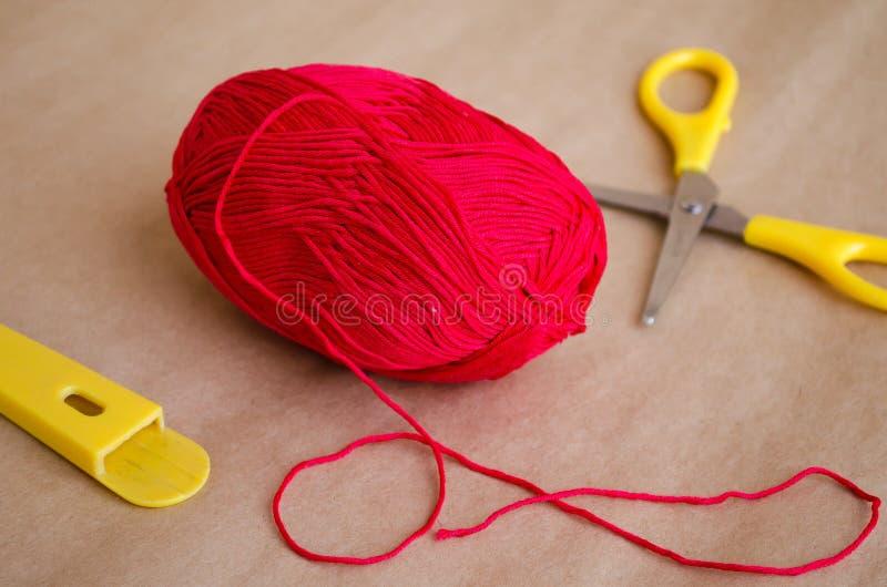 Bal van garen Een bal van rode draad Een bal van draad en schaar Rand katoenen draden stock afbeeldingen