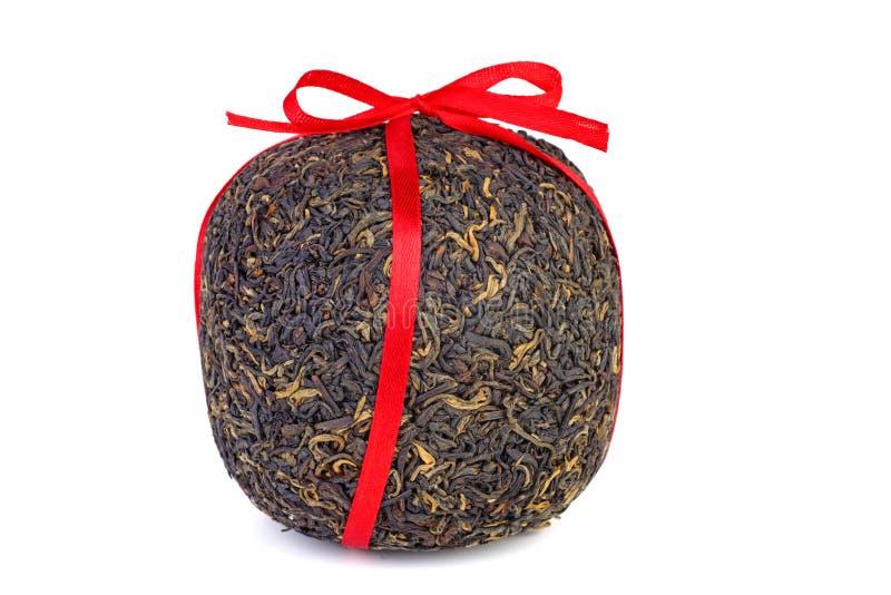 Bal van geperste zwarte chinese thee met rood lint stock foto