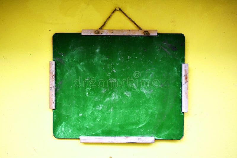 Balackboard verde che appende su una parete gialla fotografia stock