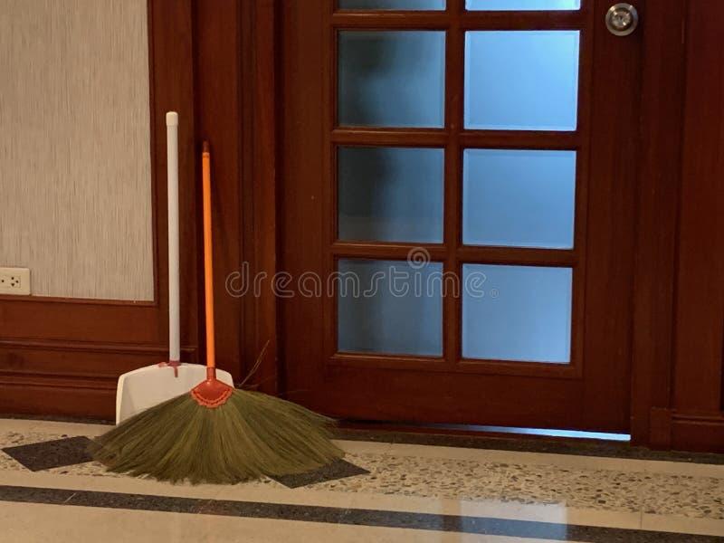 Balai avec la poignée orange et le scoop de la poudre blanche se penchant devant un équipement de nettoyage de plancher en bois d photographie stock