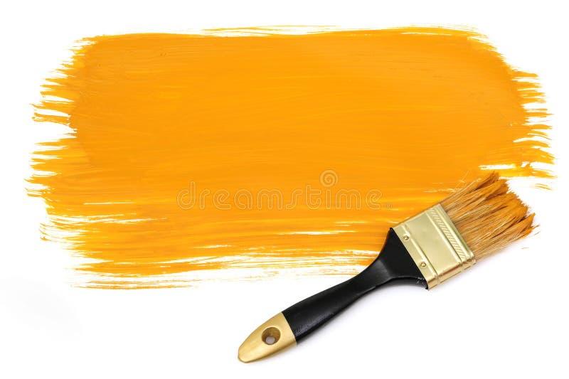 Balai et peinture jaune photographie stock