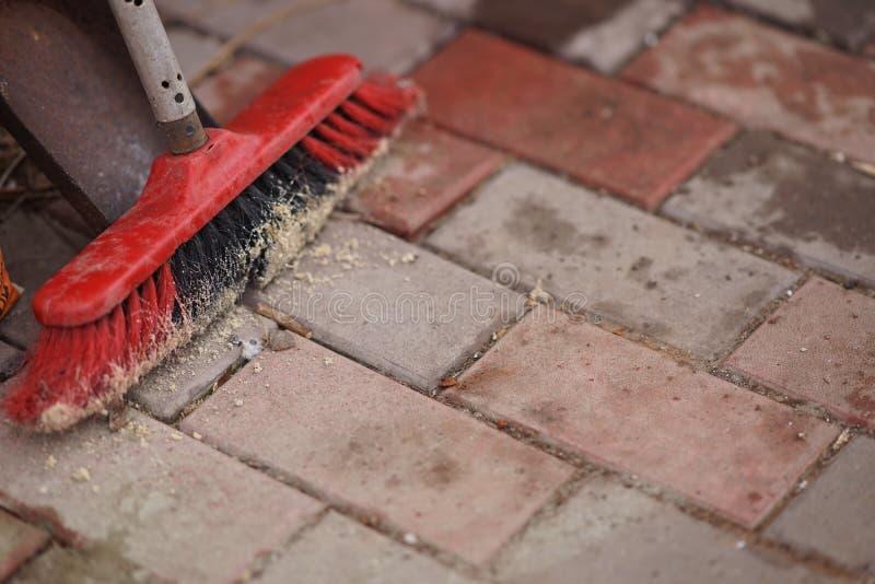 Balai et pelle à poussière sur un plancher de tuiles en pierre dans la cour photographie stock libre de droits
