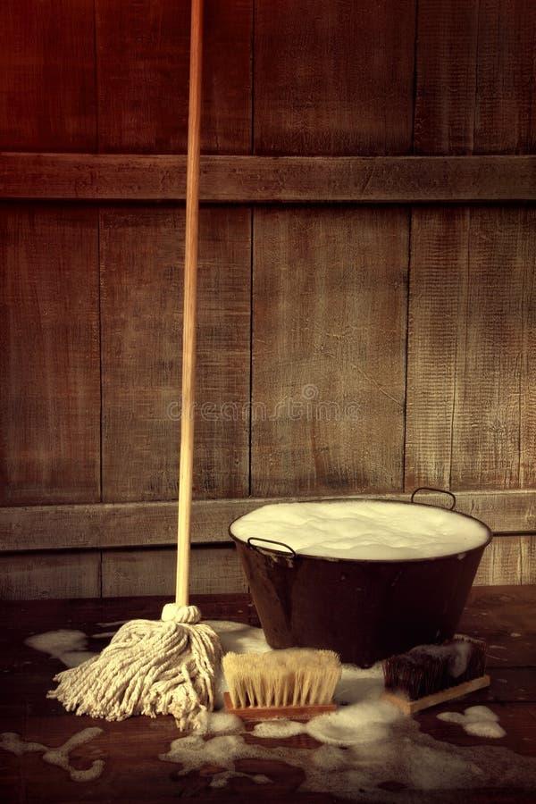 Balai et seau avec le plancher savonneux humide photo libre de droits