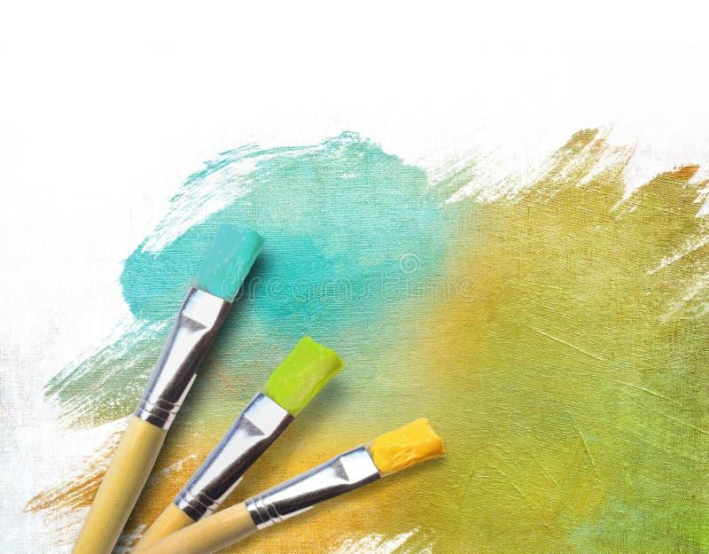 Balais d'artiste avec une toile demi-finie images stock