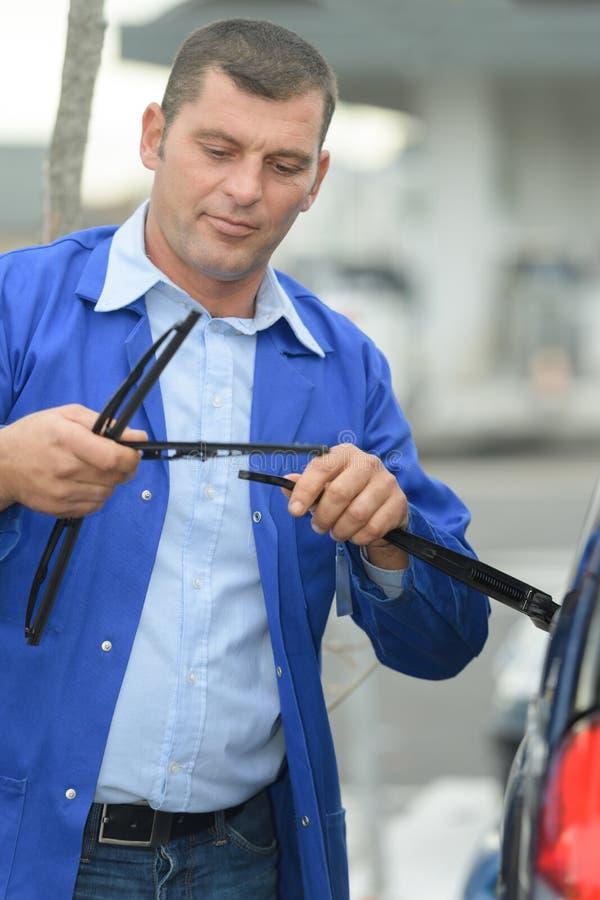Balais d'essuie-glace changeants de pare-brise de mécanicien sur la voiture image stock