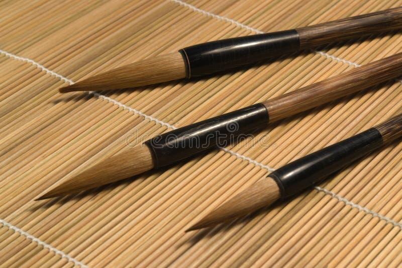Brosses de Chinois sur le détail en bois de tapis photos stock