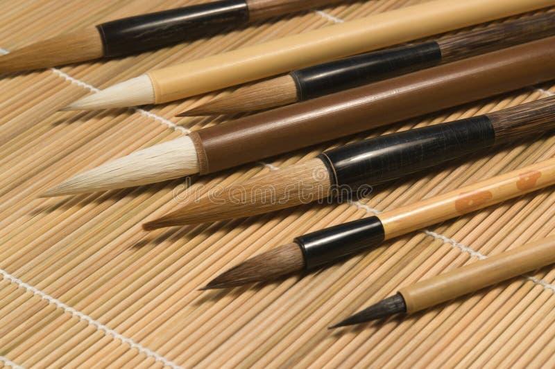Brosses de Chinois sur le détail en bois de tapis photo stock