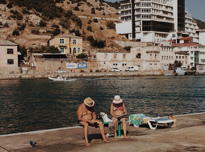 Elderly couple on sea shore of bay read newspapers royalty free stock images