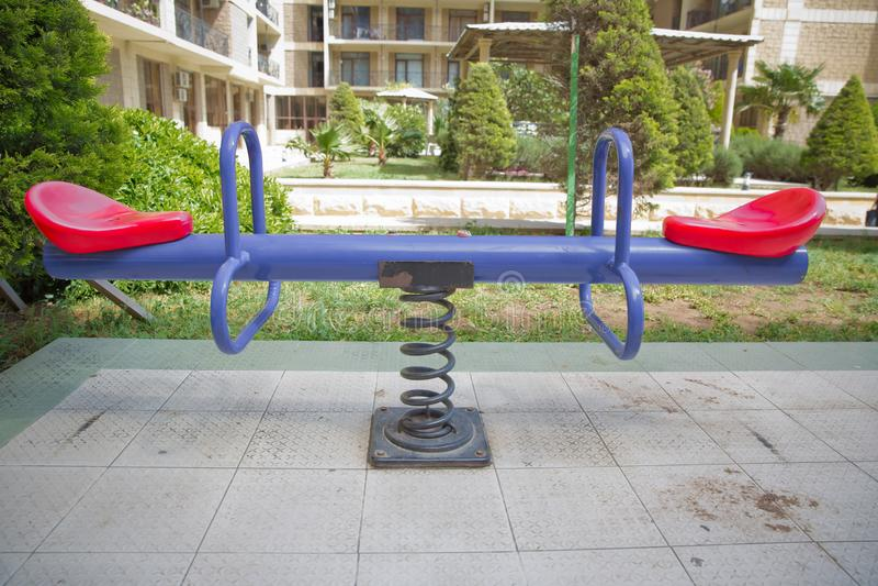 Balançar numa espiral metálica Mola de balanço de assentos duplos Novo plástico moderno, azul brilhante, colorido, e gangorra ver foto de stock