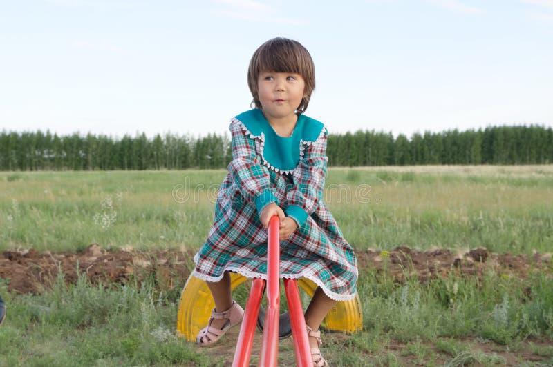 Balanço da menina na balancê no verão, criança feliz da cara engraçada no vestido verde imagem de stock royalty free