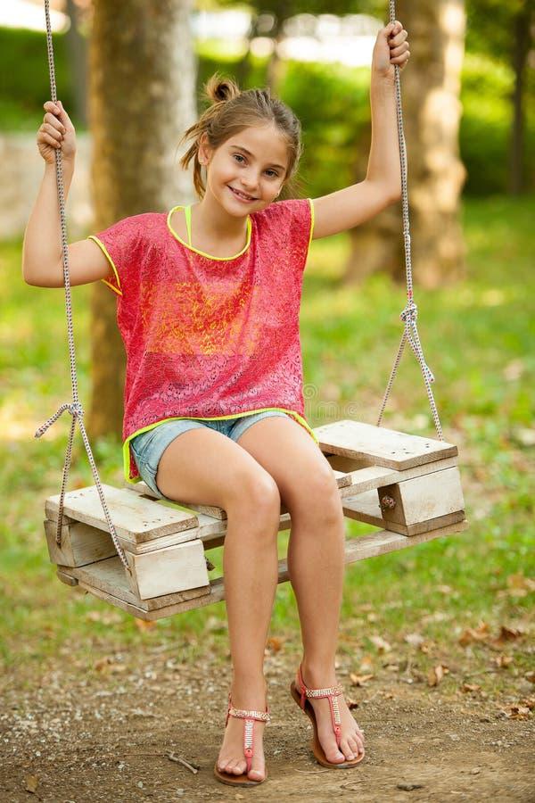 Balanço da moça exterior no parque imagem de stock