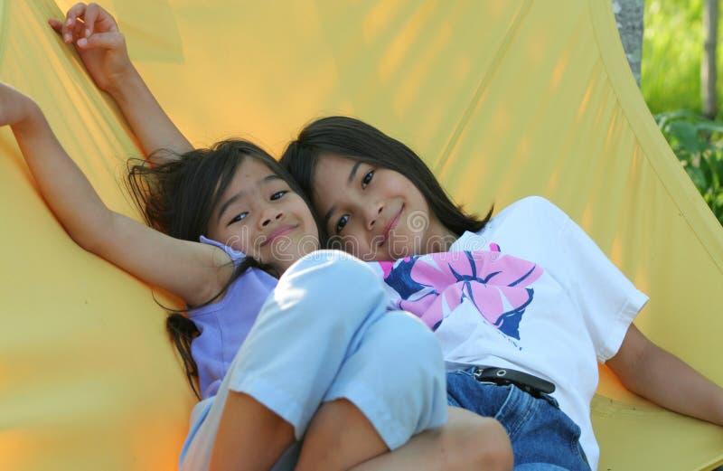 Balanço de duas meninas no hammock fotos de stock royalty free