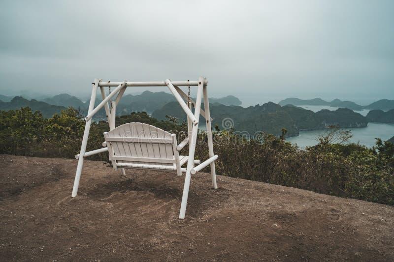 Balanço de madeira que pendura de uma árvore na praia na manhã, ilha de Cat Ba, Vietname foto de stock