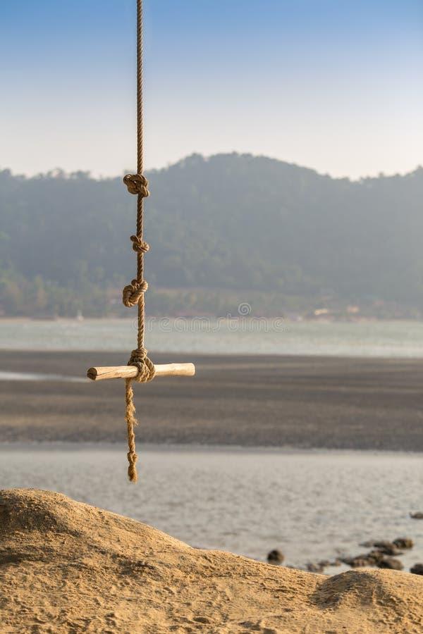 Balanço de madeira que pendura uma árvore na praia tropical - F seletivo imagem de stock