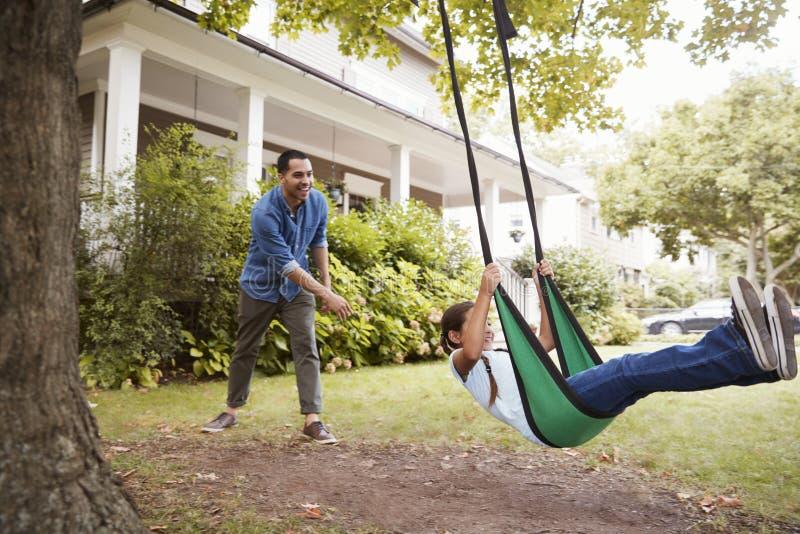 Balanço do jardim de Pushing Daughter On do pai em casa fotos de stock