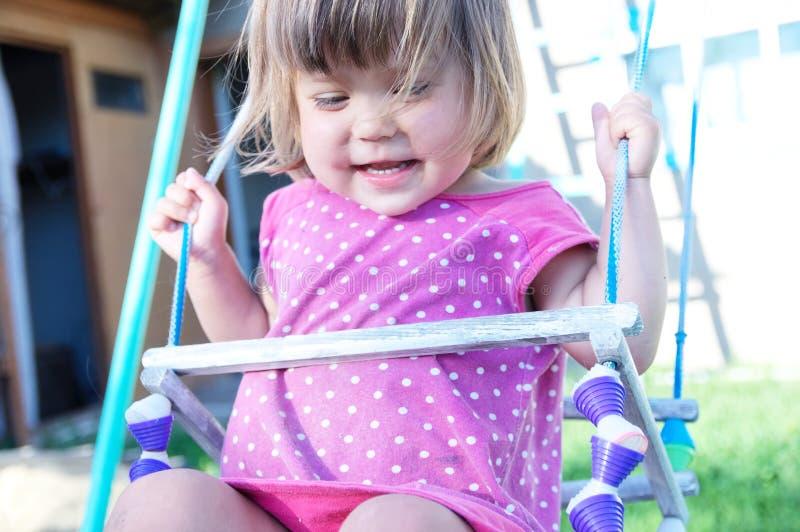 Balanço exterior, criança da menina que tem o divertimento no campo de jogos, jogo das crianças foto de stock