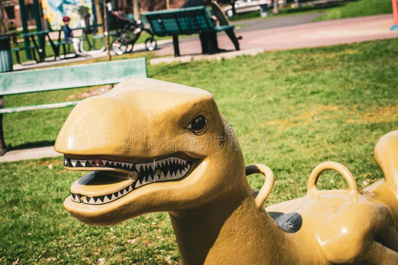 Balanço plástico do dinossauro no campo de jogos fotografia de stock