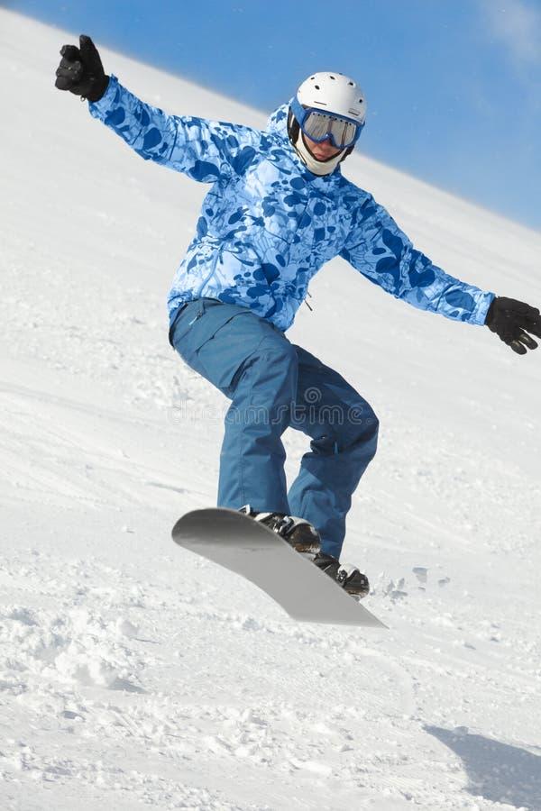 Balanços do Snowboarder quando moscas no snowboard imagem de stock