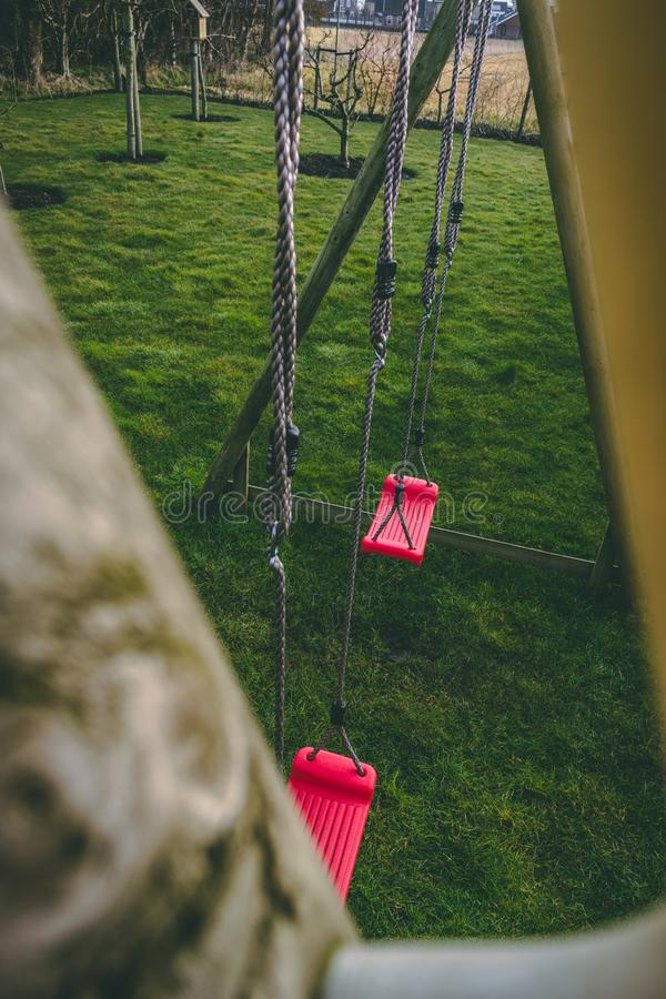 Balanços vermelhos no quintal, um campo de jogos para crianças fotos de stock