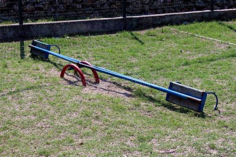 Balancê azul velha retro quebrada do campo de jogos do metal do vintage com os assentos de madeira cercados com a cerca da grama  fotos de stock