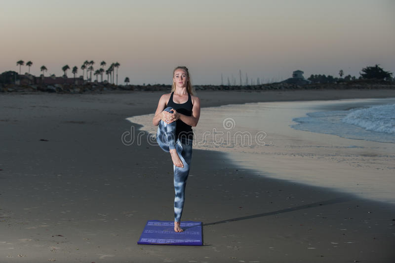 Balance conditioning under morning light. Woman holding knee lift pose on wet sand near ocean stock images