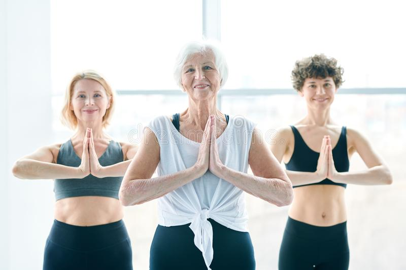 Balance and energy. Senior white-haired active women and her yoga groupmates putting their hands together by chest while keeping balance royalty free stock image