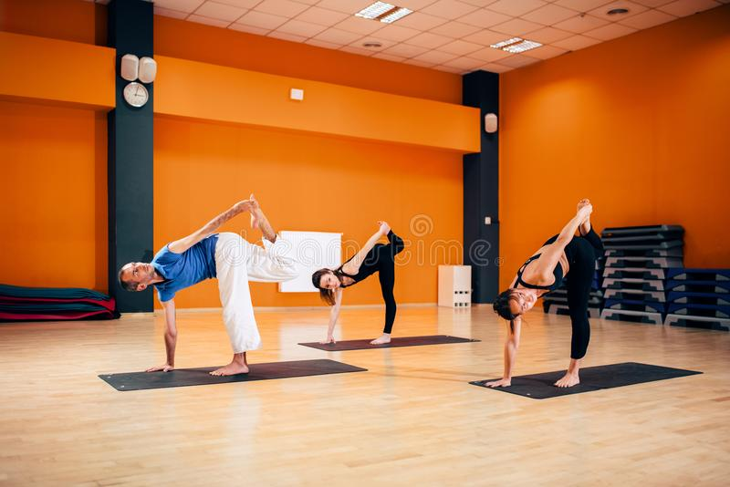 Balance exercise, female yoga group in action. Training with instructor, workout in gym. Yogi indoor stock photos