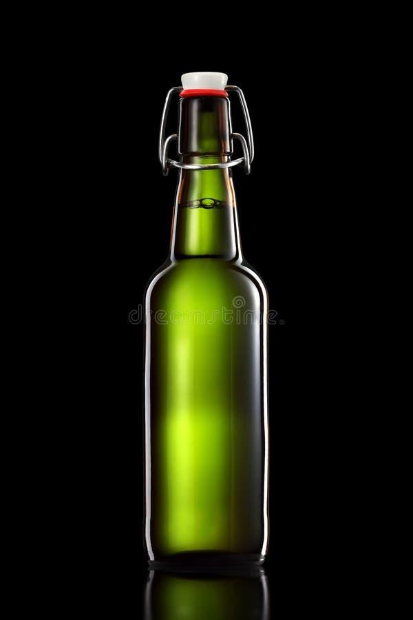 Balance a garrafa superior da cerveja clara isolada no fundo preto foto de stock royalty free