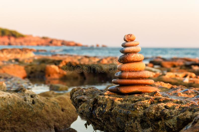 Balance and harmony. Pebbles stacked in a pyramid on the coast of the sea in nature. stock photo