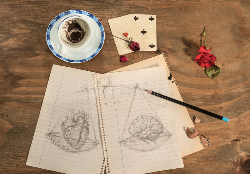 Balance:heart or brain. Empty cup with coffee grounds into a heart shape , dried rose petals,playing cards, pencil and drawing of a balance with heart and brain royalty free stock photos